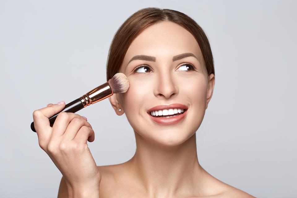Visage de femme gros plan avec un pinceau de maquillage.  Belle femme portrait beauté peau maquillage sain et parfait.  Femme appliquant un cosmétique avec un pinceau.