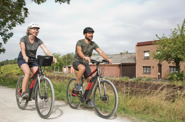 homme et femme faisant du vélo électrique décathlon riverside 500